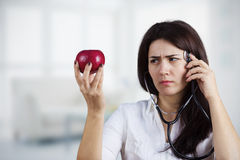 Female doctor holding red apple royalty free stock photo