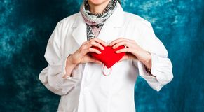 Female doctor holding a red heart. Close up stock photos