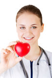 Female doctor holding red heart in hand. Royalty Free Stock Photos