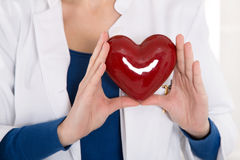 Female doctor holding a red heart in her hands - for concepts. Royalty Free Stock Photo