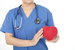 Female doctor with a red heart. A female doctor holding red heart love symbol royalty free stock photo