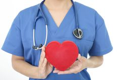 Female doctor with a red heart. A female doctor holding red heart love symbol stock photo