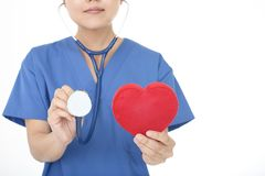 Female doctor with a red heart. A female doctor holding red heart love symbol stock photos