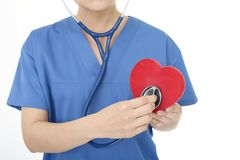Female doctor with a red heart. A female doctor holding red heart love symbol royalty free stock images