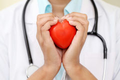 Female doctor holding a red heart shape Royalty Free Stock Image