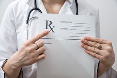 Female  doctor holding rx paper in hand Stock Photos