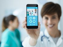 Female doctor holding a smartphone. Smiling confident female doctor holding a touch screen smartphone and medical staff on the background, medical app concept royalty free stock photos