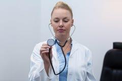 Female doctor holding stethoscope. Beautiful female doctor holding stethoscope in clinic Royalty Free Stock Photos