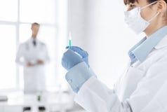 Female doctor holding syringe with injection Stock Photos
