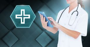 Female doctor holding tablet with medical cross interface hexagon icon royalty free stock photo