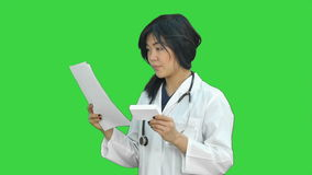 Female doctor holding up a box of tablets, smiling and presenting it on a Green Screen, Chroma Key. Close up. Professional shot in HD resolution. 080. You can stock video footage