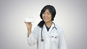 Female doctor holding up a box of tablets, smiling and presenting it on white background. Close up. Professional shot in HD resolution. 080. You can use it e.g stock video footage