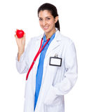 Female doctor holding up with heart ball. Isolated on white background Stock Image