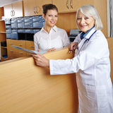 Female doctor at hospital reception. Elderly female doctor with receptionist at hospital reception royalty free stock image