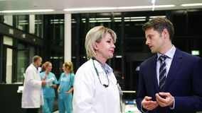 Female doctor interacting with businessman in corridor