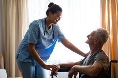Female doctor interacting with senior man in nursing home. Smiling female doctor interacting with senior men in nursing home Royalty Free Stock Images