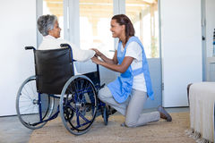 Female doctor interacting with senior woman on wheelchair. Female doctor interacting with senior women on wheelchair at home Stock Photos
