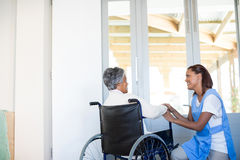 Female doctor interacting with senior woman on wheelchair Royalty Free Stock Photography