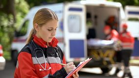 Female doctor keeping medical records, ambulance crew transporting patient stock photography