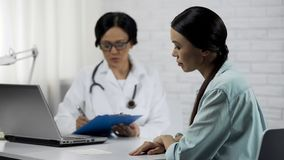 Female doctor keeping medical records attentively listening to patient symptoms royalty free stock photography