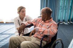 Female doctor kneeling while talking to disabled senior man on wheelchair Stock Image