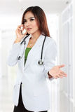 Female doctor in lab coat with stethoscope talking by cellphone Stock Photo