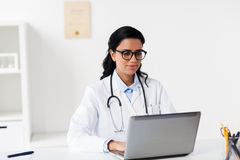 Female doctor with laptop at hospital. Healthcare, technology people and medicine concept - female doctor in white coat with laptop computer at hospital Royalty Free Stock Image