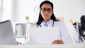 Female doctor with laptop and papers at hospital stock footage