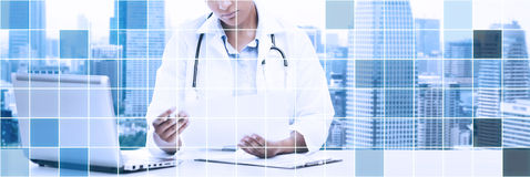 Female doctor with laptop pc looking at paper Royalty Free Stock Photography