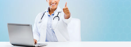 Female doctor with laptop pc showing thumbs up Royalty Free Stock Image