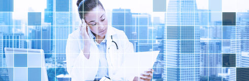 Female doctor with laptop reading medical report Royalty Free Stock Photo