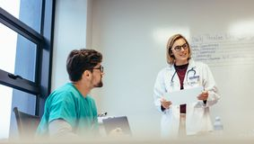 Female doctor leading meeting in hospital. Medicine professional briefing her team in boardroom royalty free stock photos