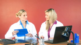 Female doctor leaving the office and shaking hands with her colleague. Attractive female doctor leaving the hospital office and shaking hands with her female stock footage