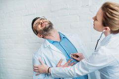 Female doctor listening to heartbeat of colleague who has heart attack. With stethoscope stock photos