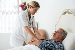 Female doctor listening to heartbeats of senior man lying on bed Stock Images