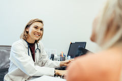 Female doctor listening to her patient during consultation. In the office. Medicine professional sitting at her desk and counselling with patient royalty free stock photo