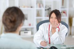 Female doctor listening to patientin office Royalty Free Stock Images