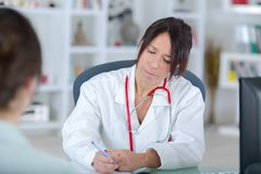 Female doctor listening to patientin office Royalty Free Stock Photography