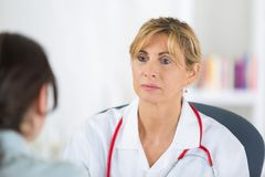 Female doctor listening to patient during consultation royalty free stock photos