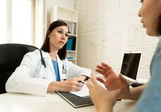 Female doctor listening to woman patient explaining her symptoms and health problems. Female family doctor listening carefully to women patient problems and stock images