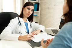 Female doctor listening to woman patient explaining her symptoms and health problems. Female family doctor listening carefully to women patient problems and royalty free stock photo