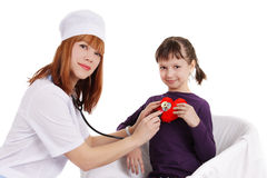 Female doctor and little girl holding plush heart Stock Photos