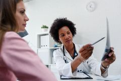 Free Female Doctor Looking At Test Results Of Her Patient. Doctor And Patient Talking Over A Medical Test Result. Royalty Free Stock Photo - 157563575