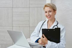 Female doctor looking at camera and working. stock photos