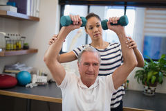 Female doctor looking at male patient lifting dumbbells Stock Images