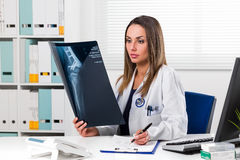 Female doctor looking at patients x-ray in her office Stock Photography