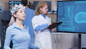 Female doctor looking at tv screen with brain activty