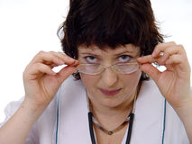 Female doctor looks over specs. Closeup of a female doctor with a serious expression looking over the top of her glasses, isolated on a white background Stock Photo