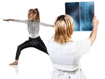 Female doctor looks on x-ray of little girl in yoga pose. Isolated on white Stock Photography