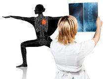 Female doctor looks on x-ray of sporty woman. Royalty Free Stock Photography